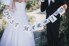 Bride-and-groom-holding-Just-married-sign