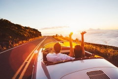 Happy-Couple-Driving-on-Country-Road-into-the-Sunset-in-Classic-Vintage-Sports-Car